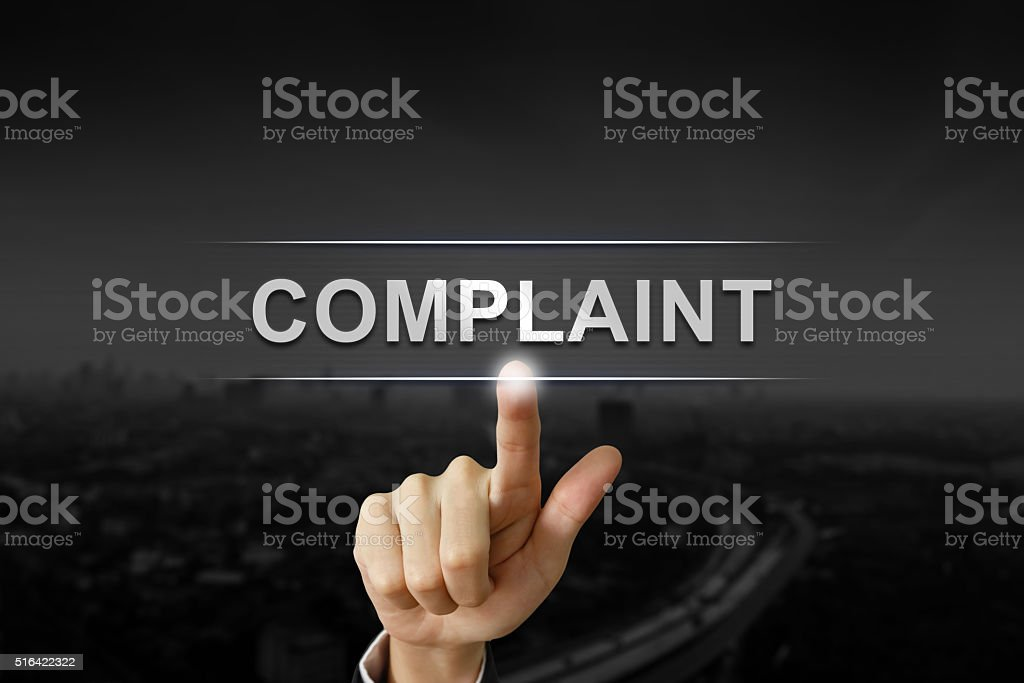 business hand pushing complaint button stock photo