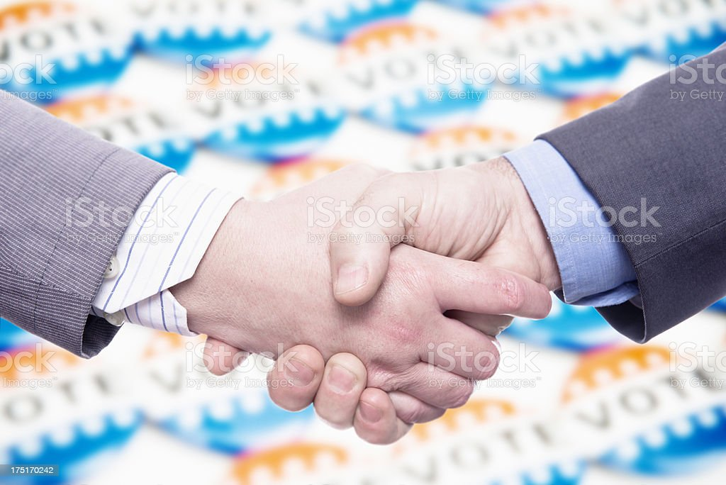 Business handshake against vote badge button royalty-free stock photo