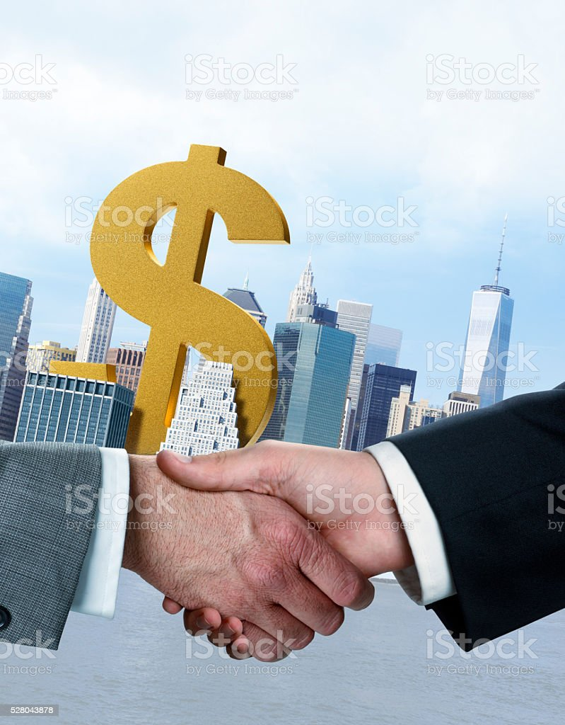 Business Handshake In Front Of Dollar Sign Standing Among Skyscrapers stock photo