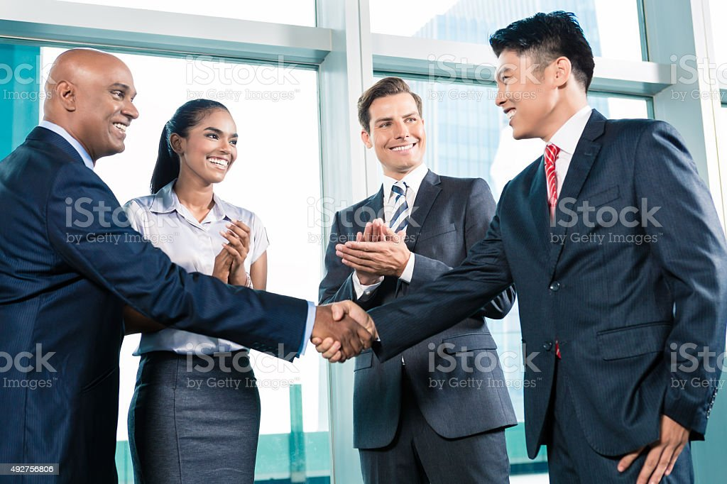 Business handshake in lofty office with city view stock photo