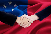 Business handshake with flag of Samoa