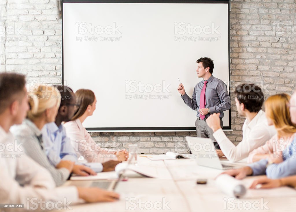 Business instructor giving presentation to large group of people stock photo