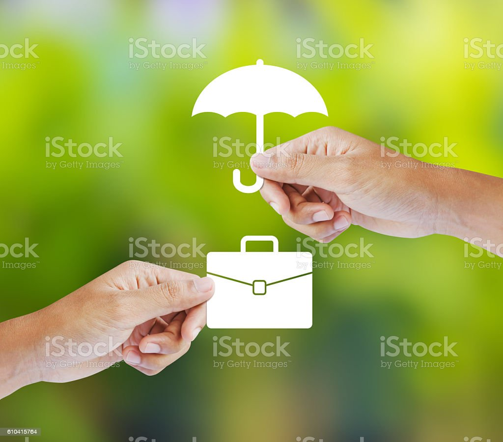 Business insurance concept with an umbrella covering business briefcase stock photo