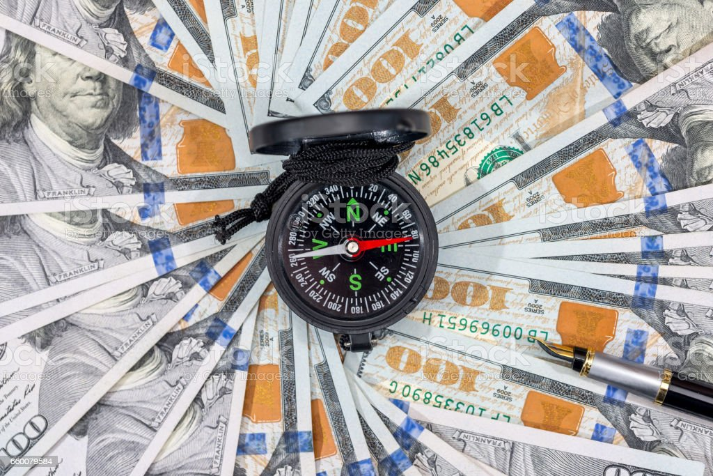 Business investment. Compass on dollar bills. close up. stock photo