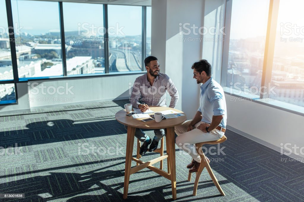 Business investors discussing business sitting at table in office stock photo