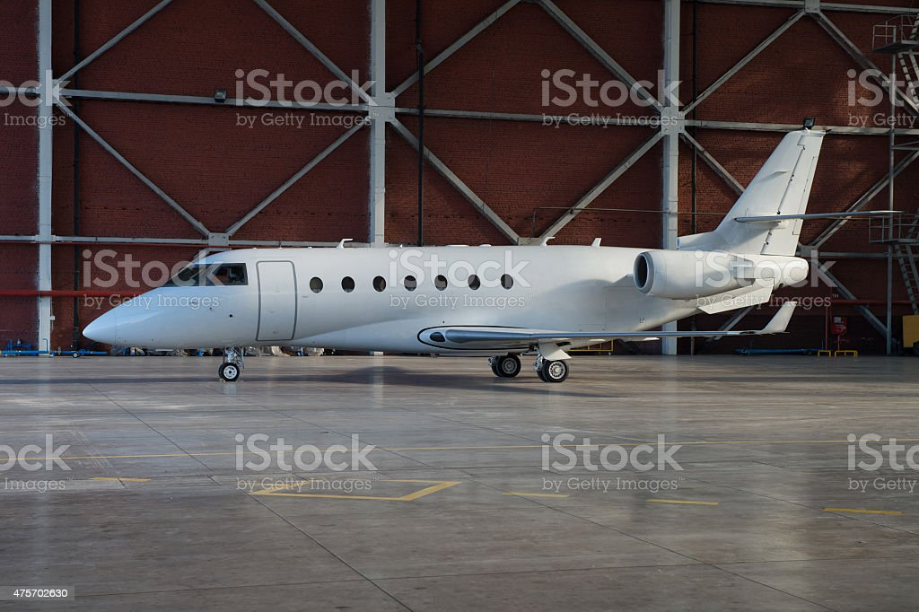 Business jet airplane is in hangar. stock photo