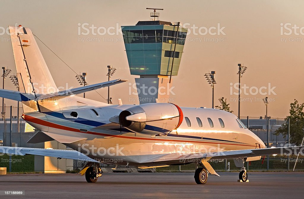 Business jet parked in front of the control tower stock photo