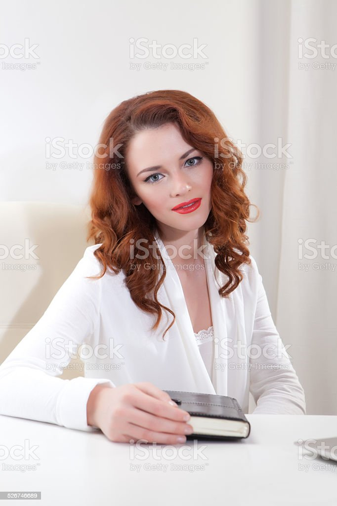 business lady in the white shirt sitting at table with stock photo