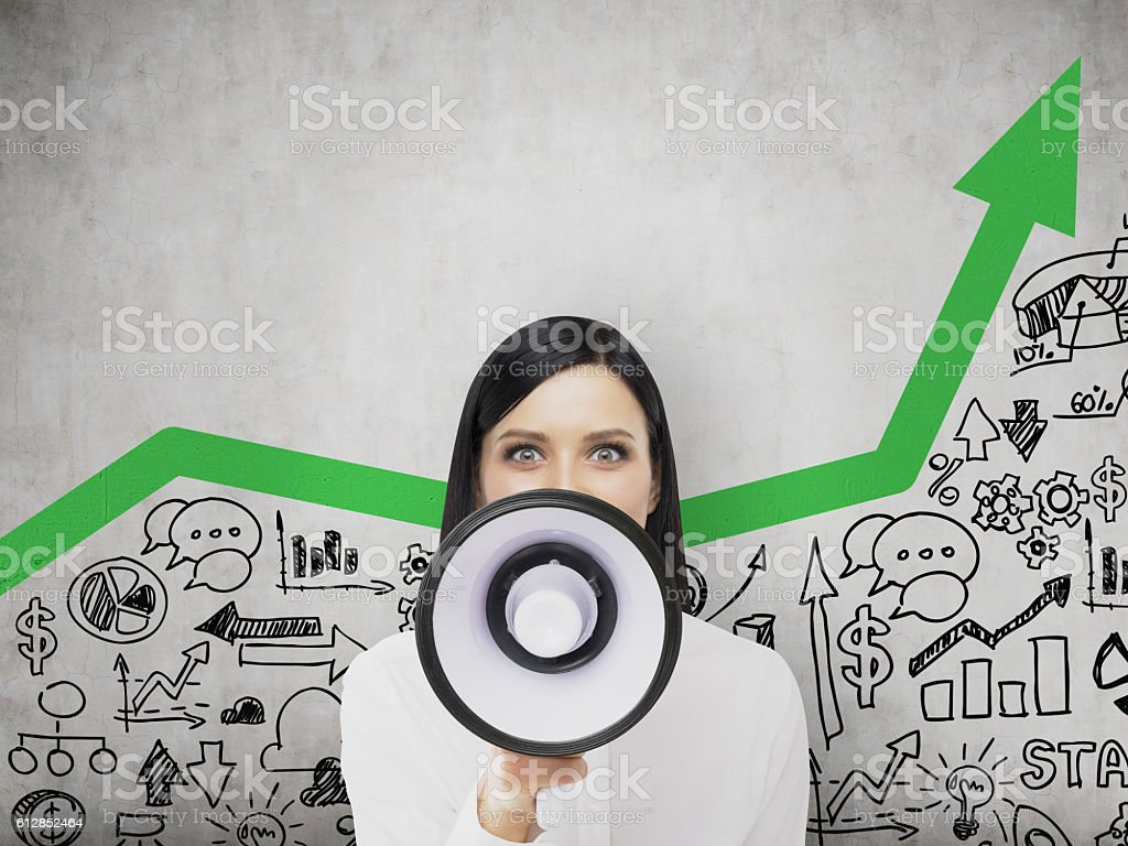 Business lady with megaphone and green arrow stock photo