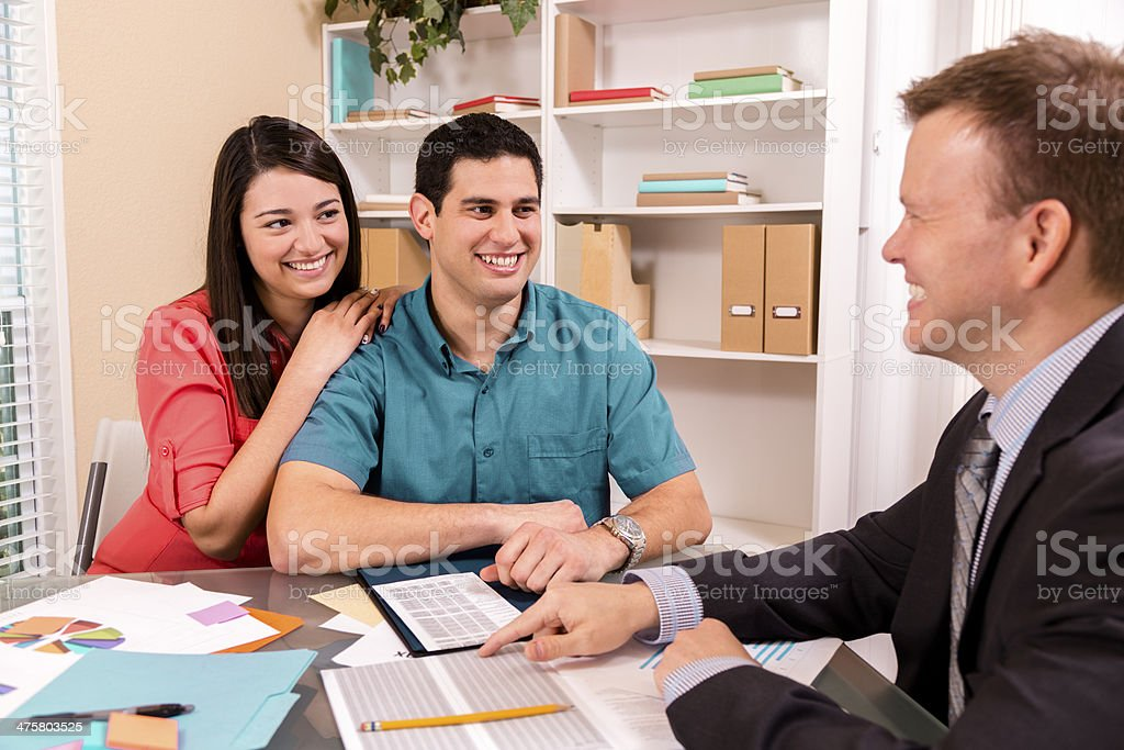 Business: Latin couple reviews financial documents with advisor. royalty-free stock photo