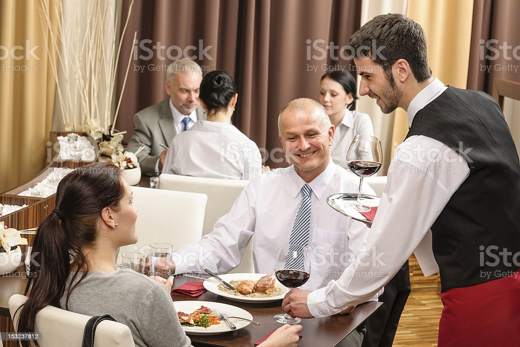 Business lunch waiter serving red wine royalty-free stock photo