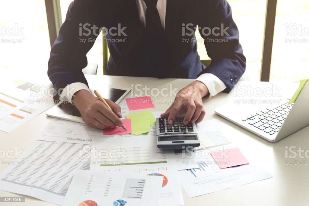 Business man analysis on data paper using calculator and laptop on white desk at the office stock photo