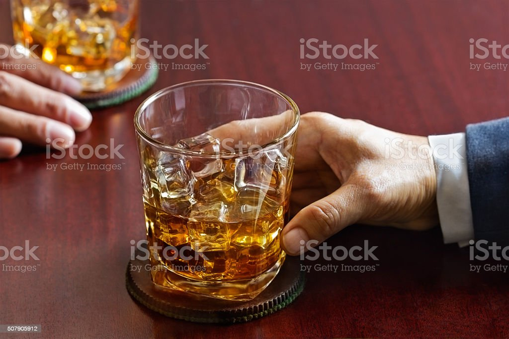 business man and whiskey in hand on wooden table bar stock photo