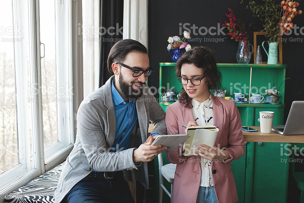 Business man and woman collaborating using tablet and notepad stock photo