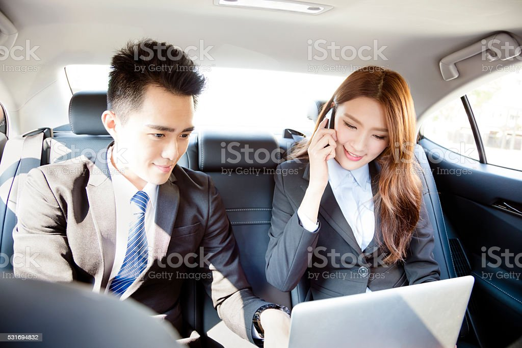 Business man and woman working together in the car stock photo