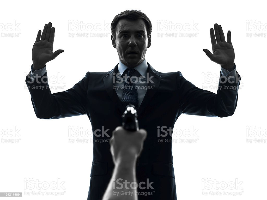 business man arms raised with gun pointing at him silhouette stock photo