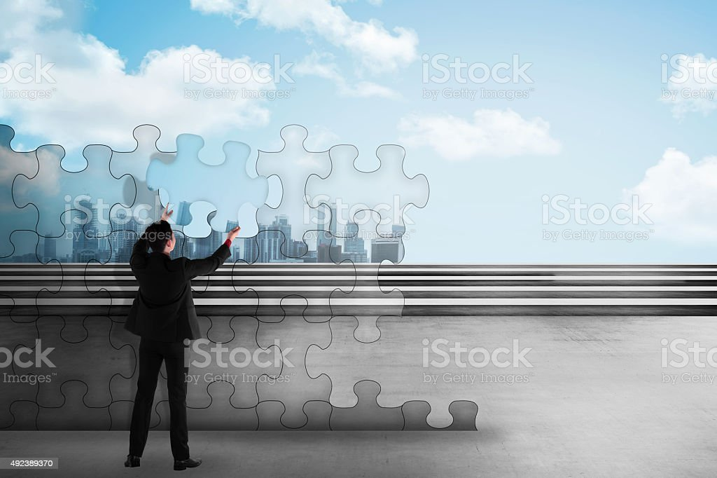 Business man assemble puzzle trying to build a city stock photo