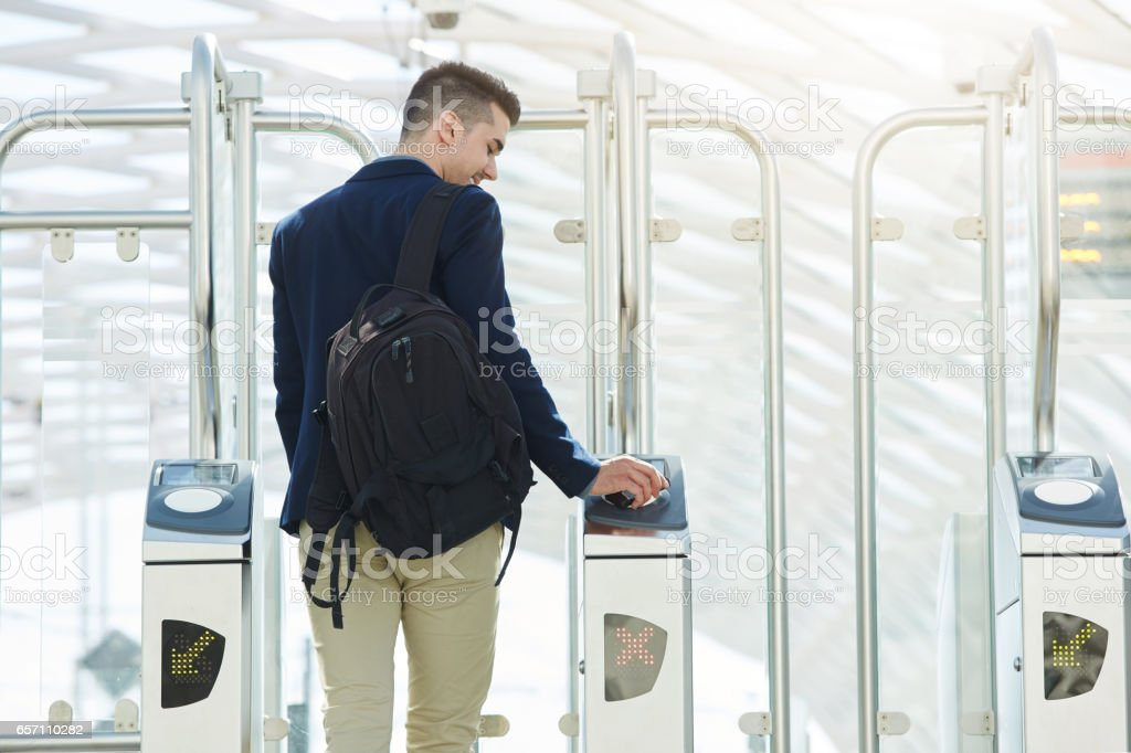 business man at automated turnstile with cellphone stock photo