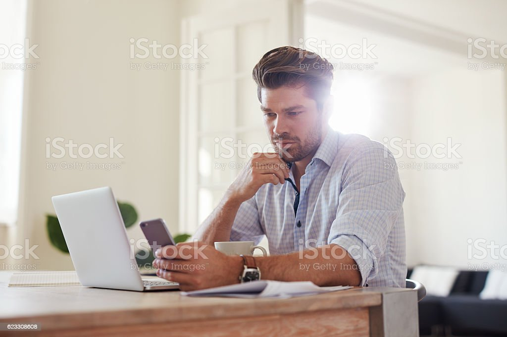 Business man at home office with smart phone and laptop stock photo