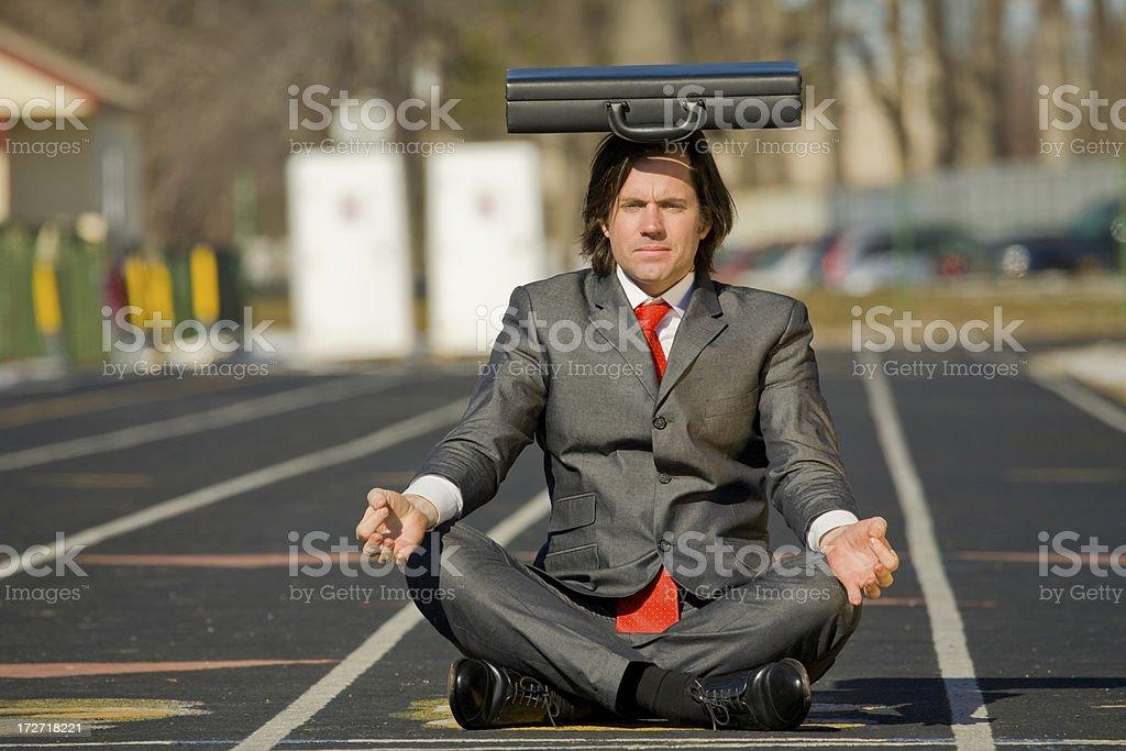 Business man balances briefcase on head royalty-free stock photo