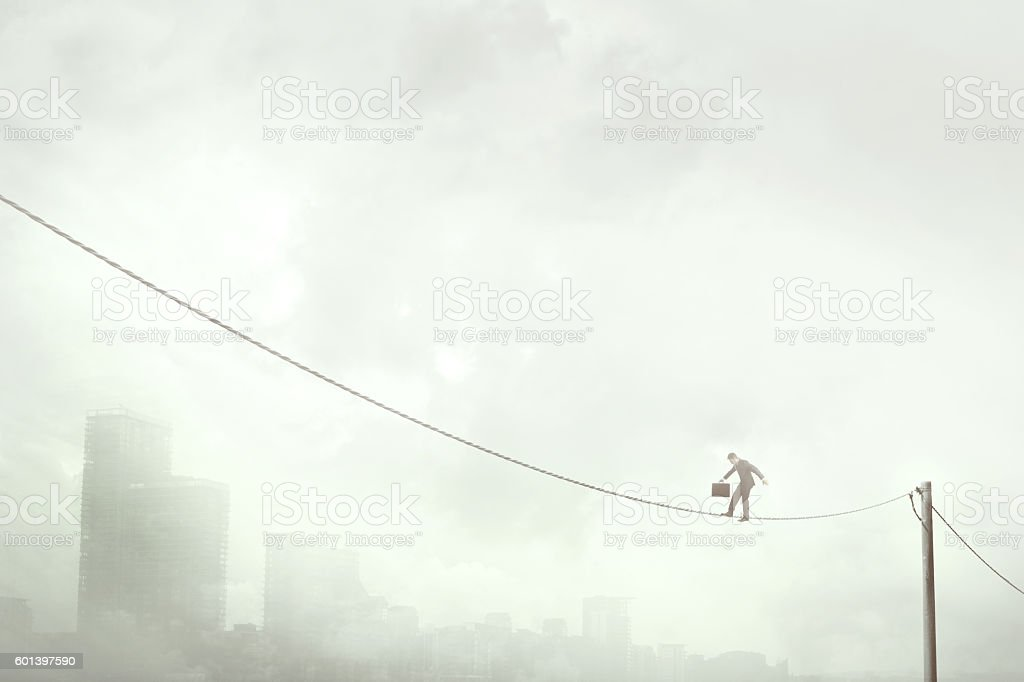 business man balancing on a electric wire over the city stock photo
