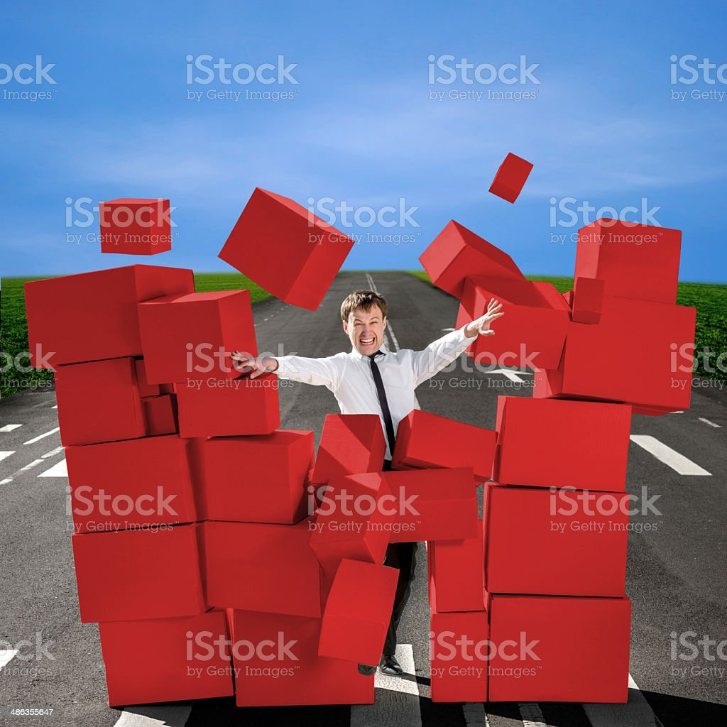 Business man breaking the wall of carton boxes stock photo
