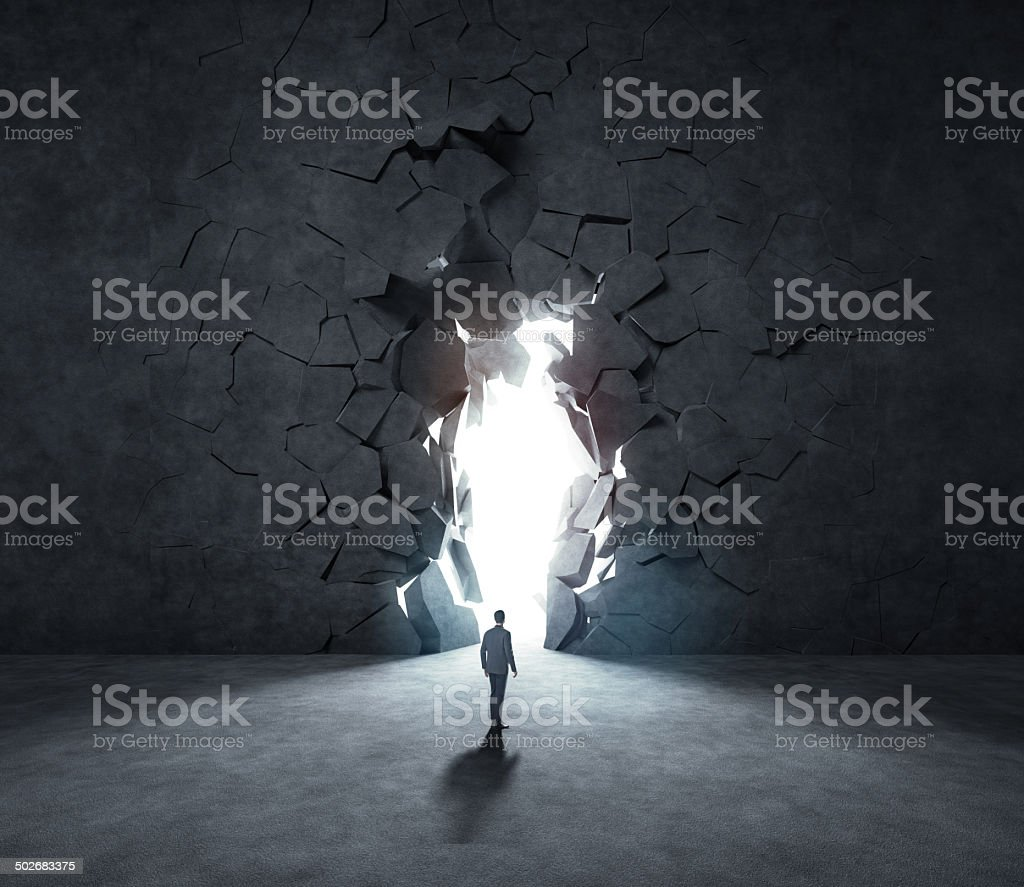 business man breaking trough a stone wall stock photo