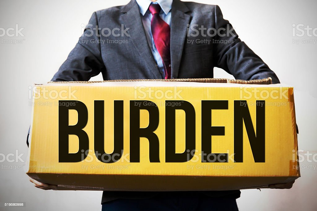Business man carrying an old box saying 'BURDEN' stock photo