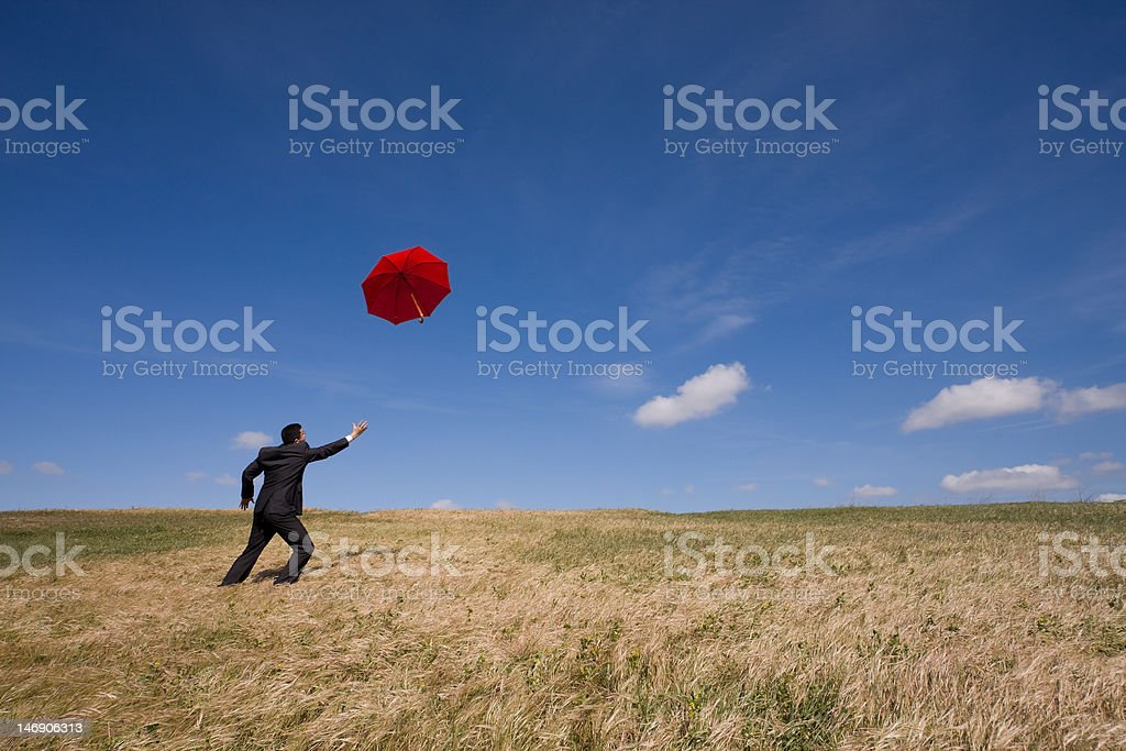Business man chasing umbrella royalty-free stock photo