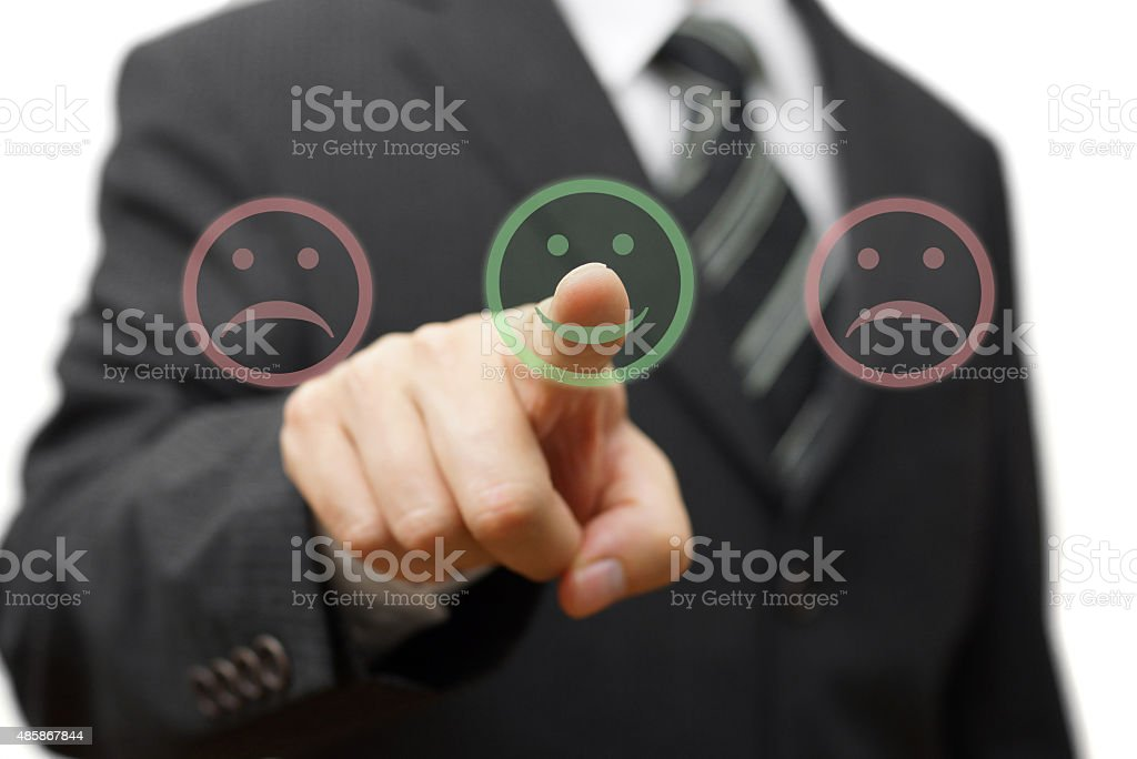 Business man choose  smile icon  and not the sad one stock photo