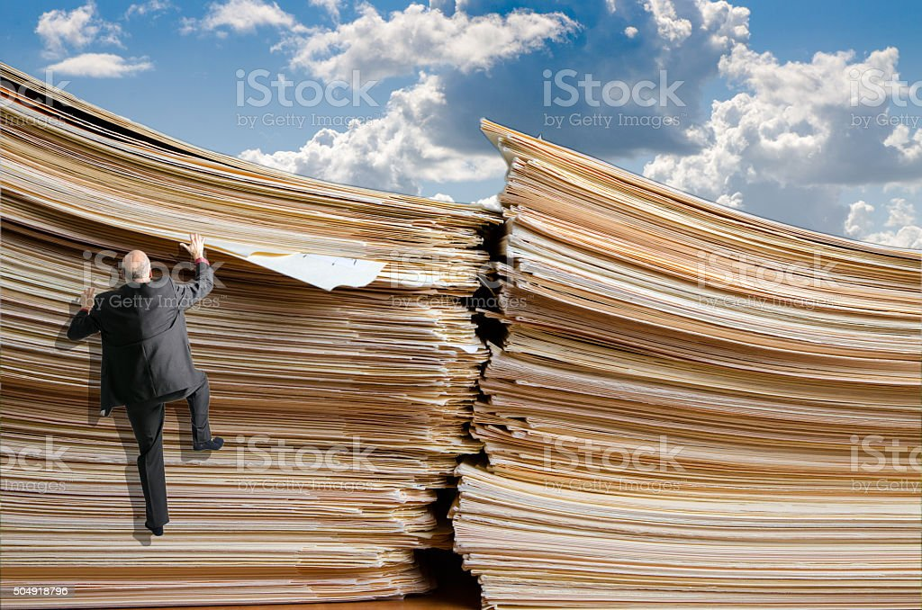 Business man climbing up a pile of files stock photo