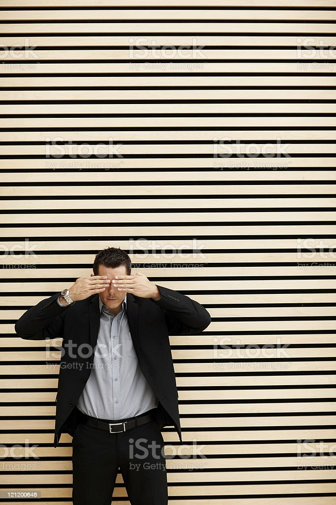 Business man covering eyes with his hands stock photo