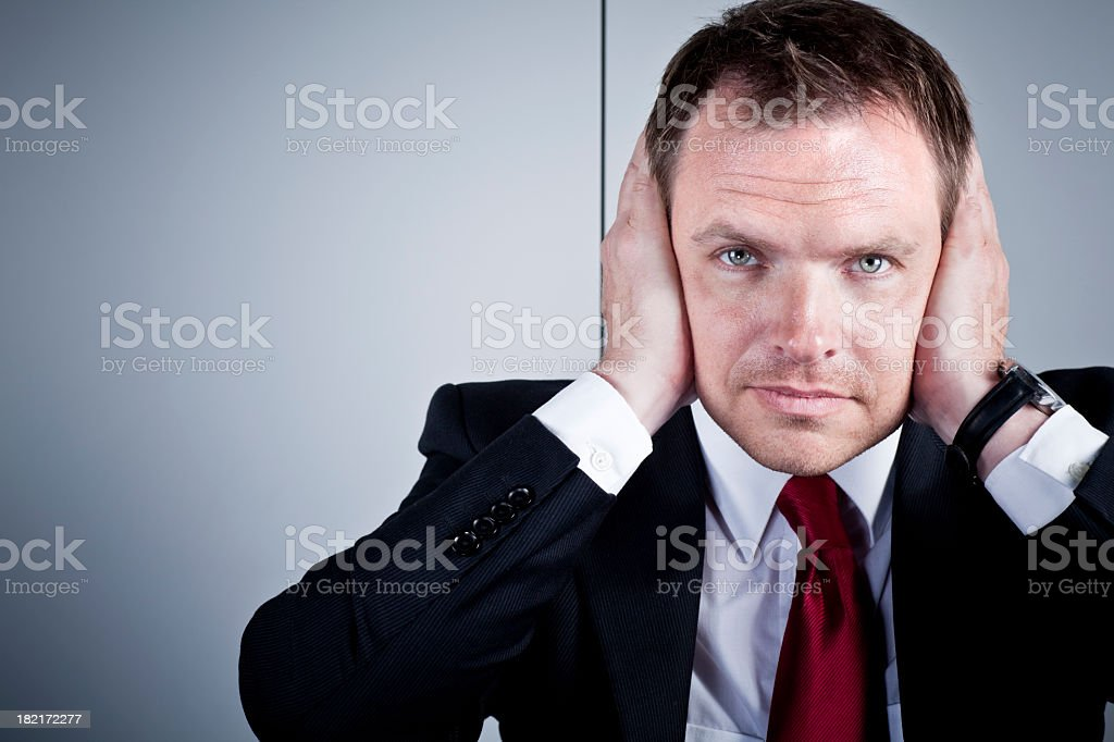Business man covering his ears stock photo
