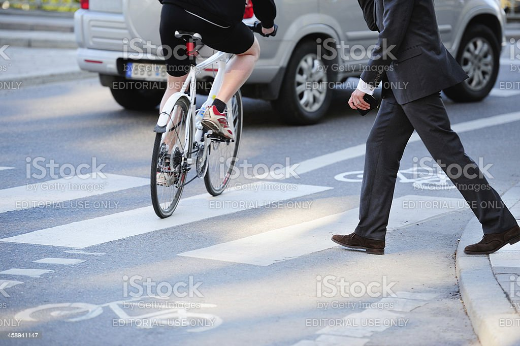 Business man crossing street in traffic stock photo