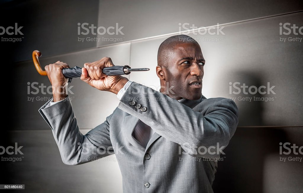 Business Man Defends Himself with His Umbrella stock photo
