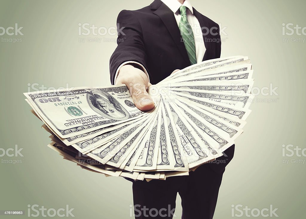Business Man Displaying a Spread of Cash stock photo