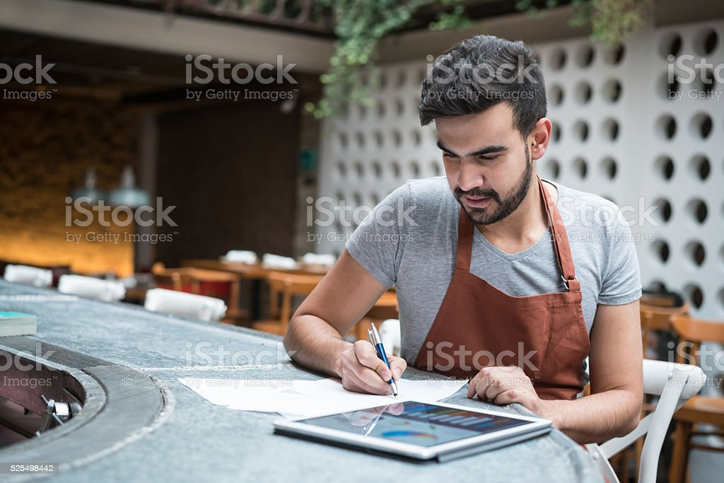 Business man doing the books at a restaurant stock photo