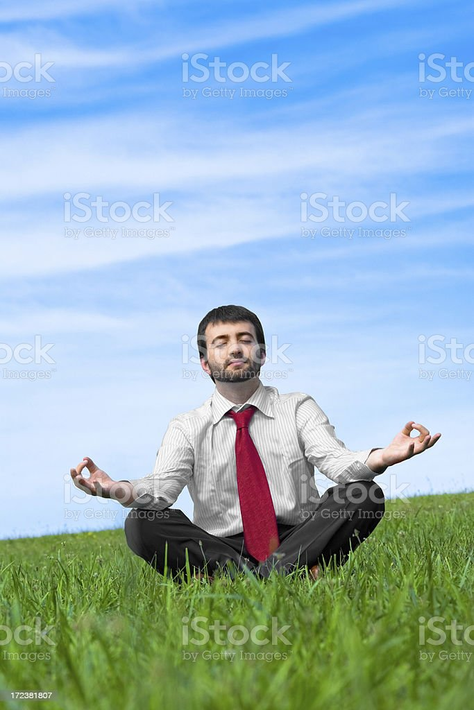 business man doing yoga in grass field royalty-free stock photo
