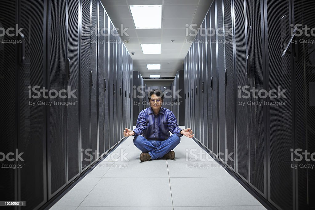 A business man doing yoga in the network server room  stock photo