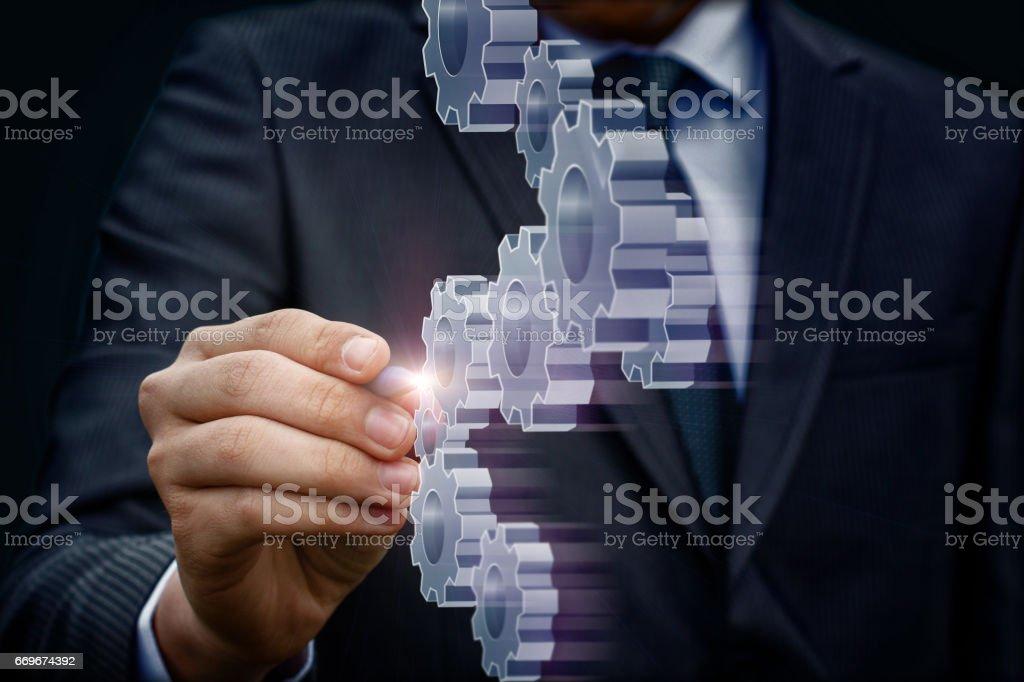 Business man draws gear mechanism. stock photo