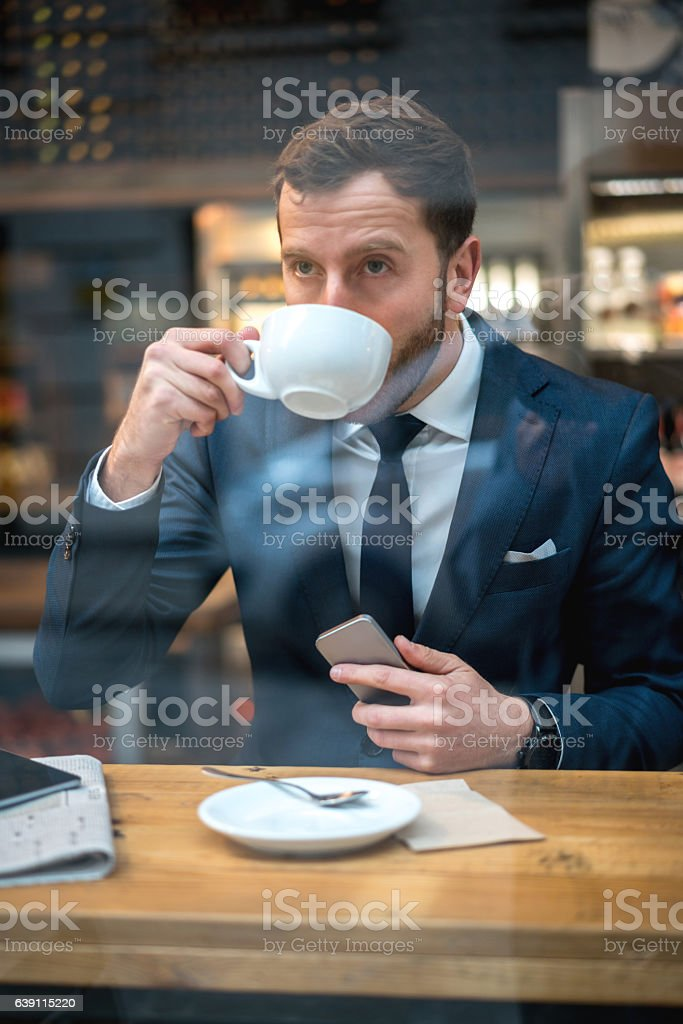 Business man drinking a cup of coffee stock photo