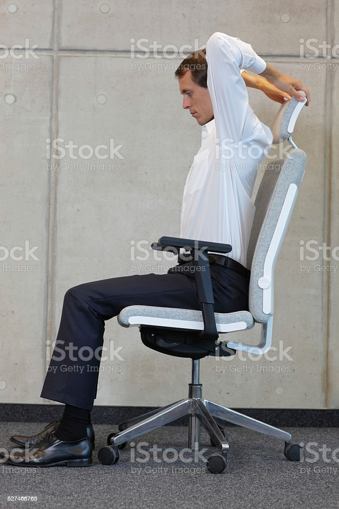 business man exercising on armchair - yoga office stock photo