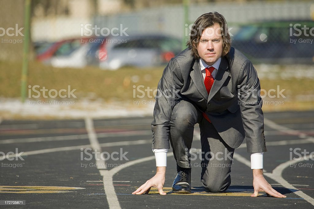 Business man gets ready to run on track royalty-free stock photo