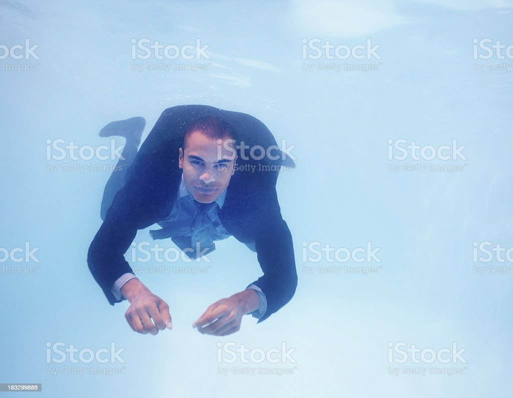 Business man getting refreshed under water in pool - copyspace stock photo