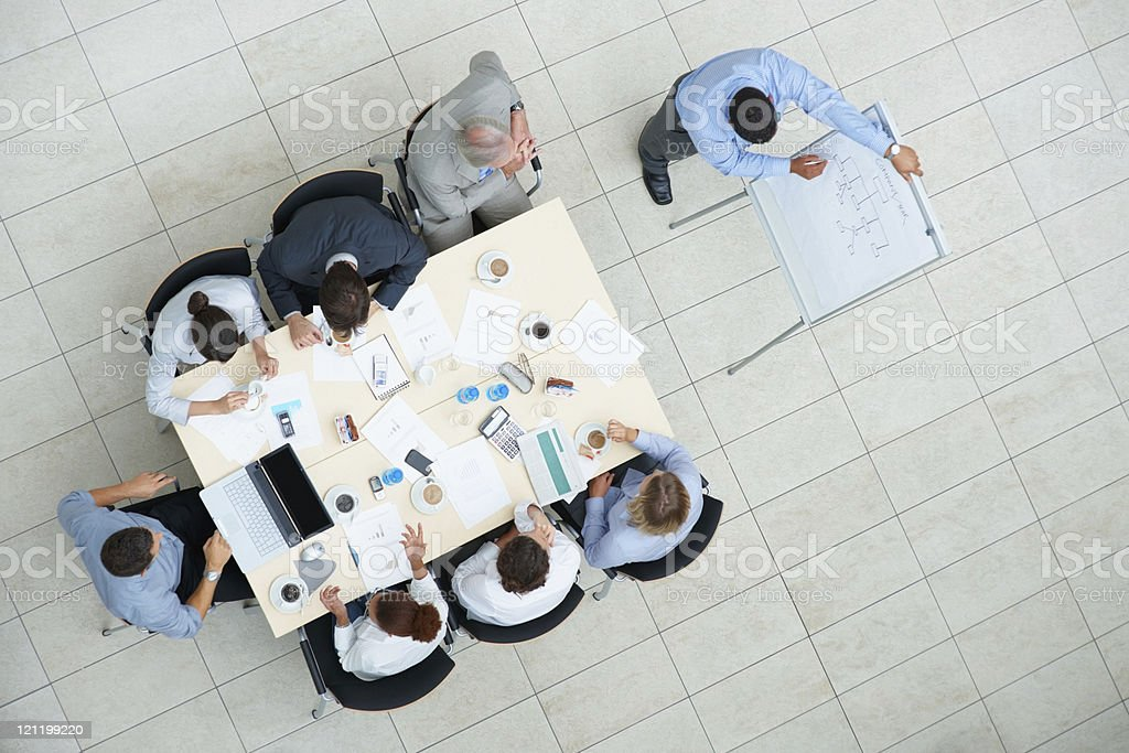 Business man giving a presentation to colleagues at meeting royalty-free stock photo