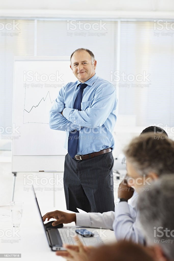 Business man giving a presentation to his team royalty-free stock photo