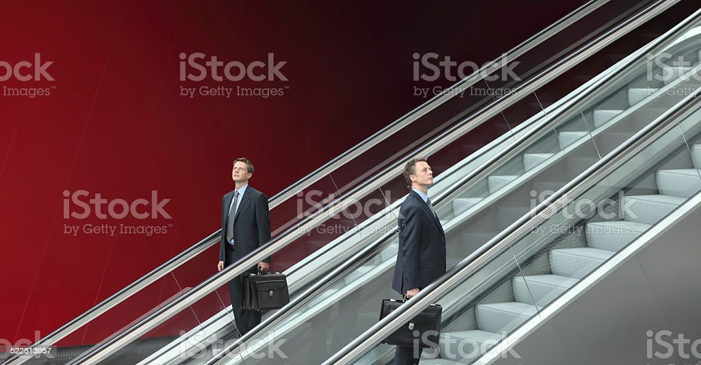 business man going up and down escalators, concept of choice stock photo