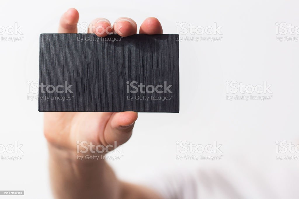 Business man, guy, designer, freelancer handing a  parchment visiting  blank black business card, white background, name, mock up, free space stock photo