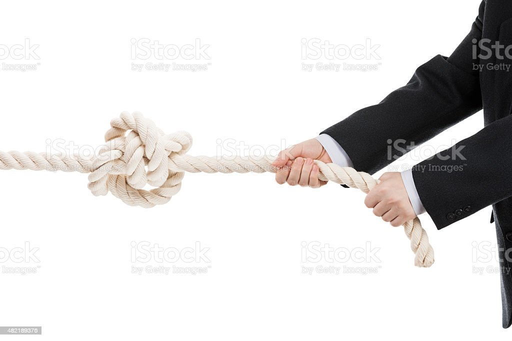 Business man hand holding or pulling rope with tied knot stock photo