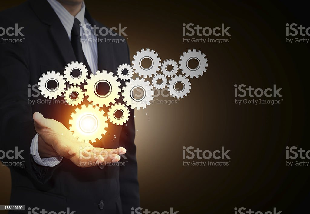 Business man hand show gear to teamwork as concept stock photo